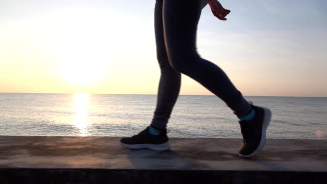 vídeos y material grabado en eventos de stock de slo mo hermosa jovencita asiática corriendo en la playa de arena - encuadre cintura para arriba
