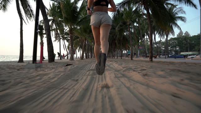 vidéos et rushes de belle jeune femme asiatique exécutant sur la plage de sable - matin