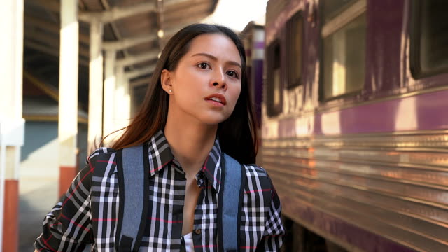 beautiful young asian woman tourist is solo traveling and walking alone at the train station. - railway station platform stock videos & royalty-free footage