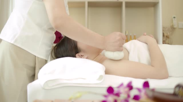vídeos de stock e filmes b-roll de beautiful young asian woman with facial mask ,body massage ,hand and body treatment,foot massage,warm herb massage at beauty spa salon. looking relaxed while getting a massage from a professional masseuse beauty treatments, health. 4k video slow motion. - spa treatment