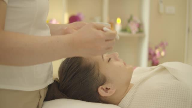 vidéos et rushes de belle jeune femme asiatique avec le masque facial, massage de corps, traitement de main et de corps, massage de pied, massage chaud d'herbe au salon de spa de beauté. vous cherchez détendu tout en obtenant un massage d'une masseuse professionnelle be - spa