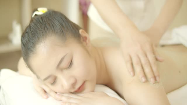 beautiful young asian woman with facial mask ,body massage ,hand and body treatment,foot massage,warm herb massage at beauty spa salon. looking relaxed while getting a massage from a professional masseuse beauty treatments, health. 4k video slow motion. - lastone therapy stock videos & royalty-free footage