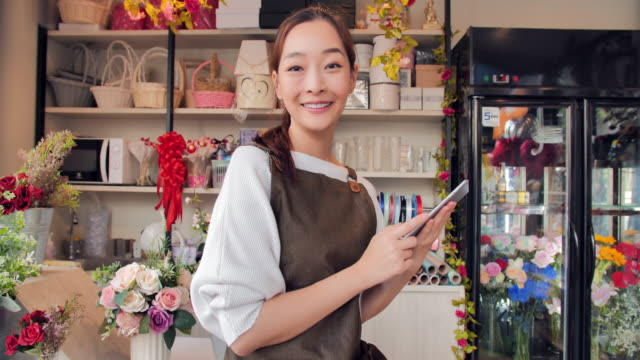 beautiful young asian woman working using tablet computer and smiling while sitting in workshop. - fioraio negozio video stock e b–roll