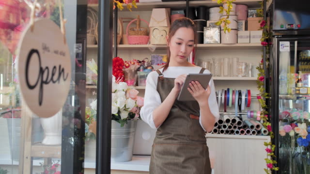 beautiful young asian woman working using tablet computer while standing in workshop.technology, lifestyles,entrepreneurship, vision, innovation, opportunity, small business, wisdom, independence, collaboration, leadership, success, service concept. - fioraio negozio video stock e b–roll