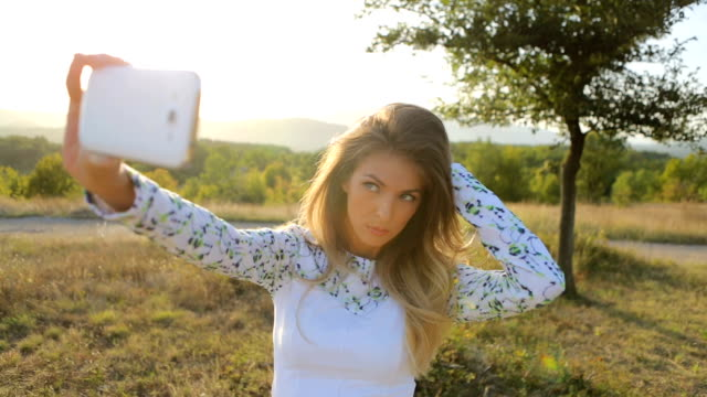 Beautiful young blonde woman having fun, using smart phone and doing photo and selfie in the field