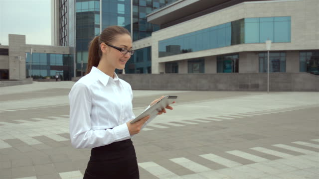 vídeos de stock e filmes b-roll de bela jovem mulher de negócios com óculos a falar sobre tablet - criação animal