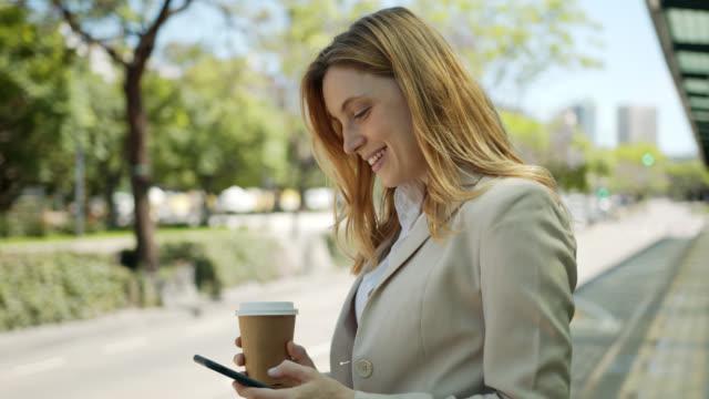 vídeos de stock, filmes e b-roll de a mulher de negócio nova bonita que texting em seu smartphone que espera a barra-ônibus e que aprecia um toma para fora o café - viagem de negócios