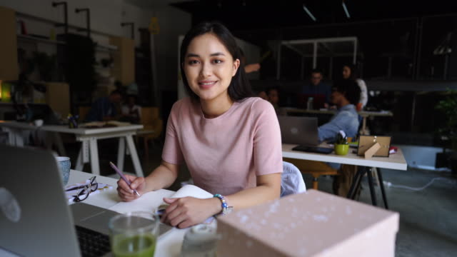 beautiful young businesswoman sitting cheerfully in co-working space - copy space stock videos & royalty-free footage