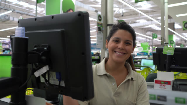 beautiful young cashier at a supermarket  typing something on screen and then smiling at camera - cashier stock videos & royalty-free footage