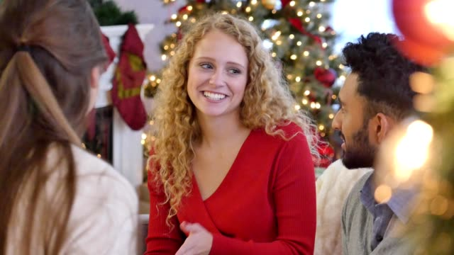 beautiful young caucasian woman smiles and laughs while talking with her friends at a christmas party - christmas wrapping paper stock videos & royalty-free footage