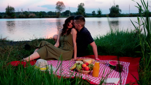 Beautiful young couple kissing sitting on picnik blanket