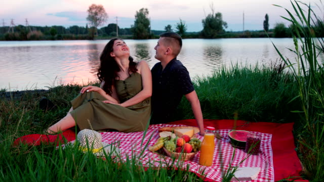 Beautiful young couple laughing together sitting on picnik blanket