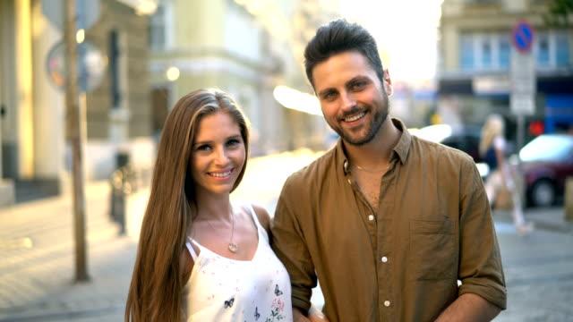 美しい若いカップルを探して、カメラで笑顔