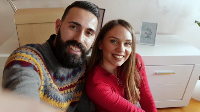 vidéos et rushes de beau jeune couple faisant le selfie dans le nouvel appartement - la vingtaine