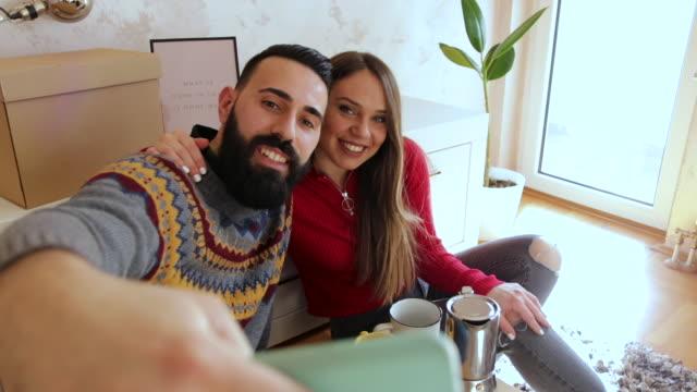 vídeos y material grabado en eventos de stock de hermosa pareja joven haciendo selfie en nuevo apartamento - eventos de la vida