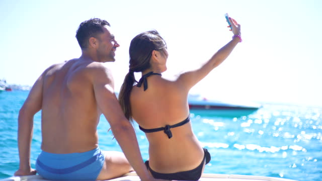 beautiful young couple relaxed in yatch and taking a selfie - men's underpants stock videos and b-roll footage