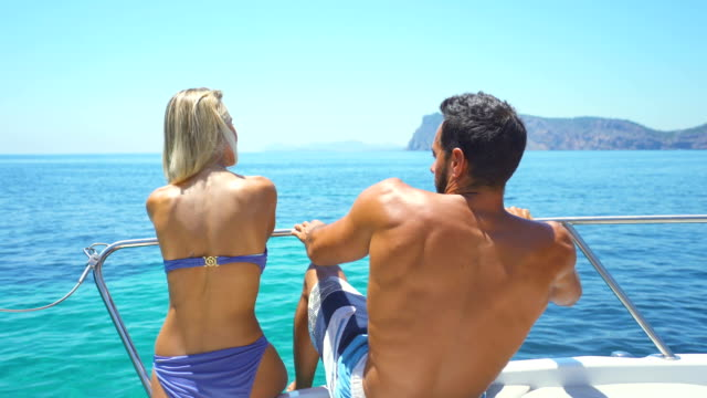 stockvideo's en b-roll-footage met beautiful young couple relaxed in yatch - ontbloot bovenlichaam