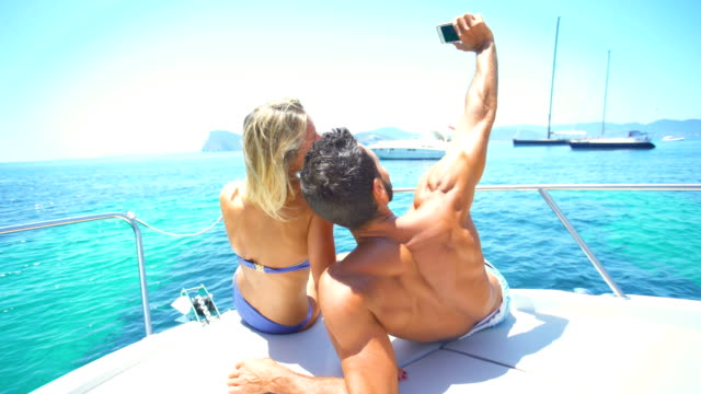 vídeos de stock e filmes b-roll de beautiful young couple relaxed in yatch - barco