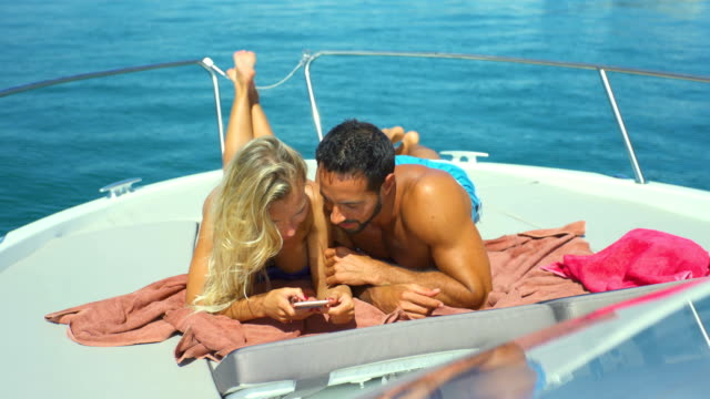 beautiful young couple relaxed in yatch watching smartphone - semi dress stock videos & royalty-free footage