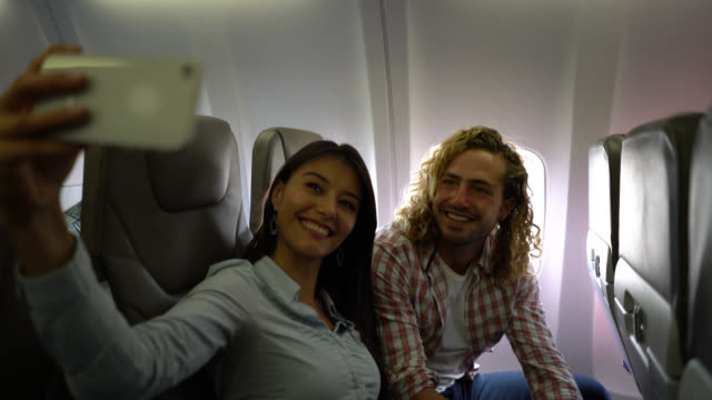 Beautiful young couple taking a selfie while seating at the airplane both smiling