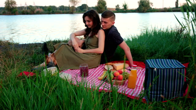 Beautiful young couple with Yorkshire Terrier on picnic near river