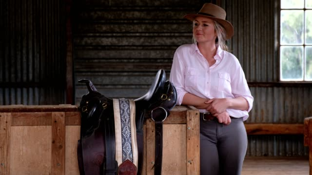 beautiful young cowgirl standing in the barn - cattle drive stock videos & royalty-free footage