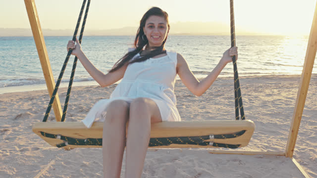 beautiful, young, egyptian woman on a swing at the red sea coast near hurghada while her vacation having big fun. - red sea stock videos & royalty-free footage