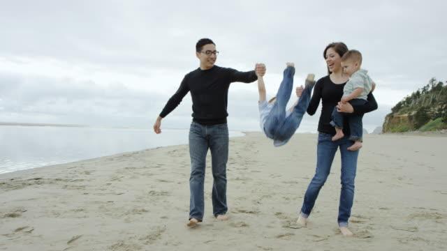 Mooie jonge etnische familie wandelen op het strand