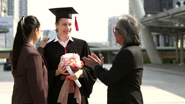 vídeos y material grabado en eventos de stock de hermosa joven diplomado hembra con los padres en la ceremonia. - gorra