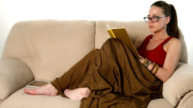 schöne junge frau bequem auf der couch liegen und ein buch zu lesen - buchdeckel stock-videos und b-roll-filmmaterial