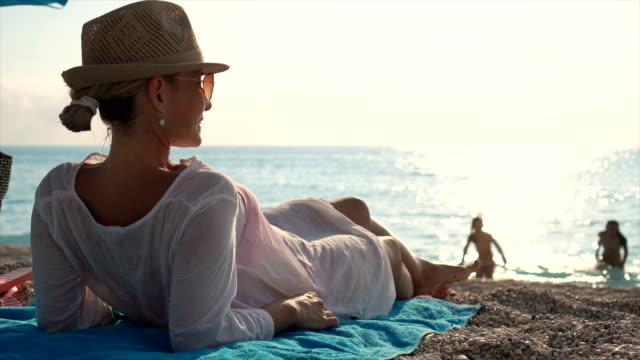 schöne junge frau am strand sitzen auf einem strand zum sonnenbaden. - hängematte stock-videos und b-roll-filmmaterial