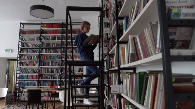 beautiful young female student at the library walking up stairs to reach a book at the library - book shop stock videos & royalty-free footage