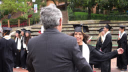 Beautiful young female student hugging her dad after receiving her degree at college