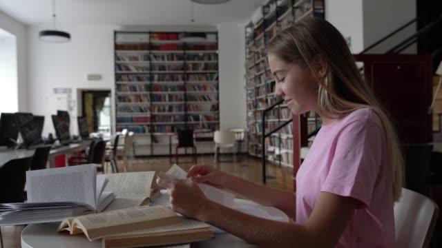 Schöne junge Studentin liest ein Buch und kichert