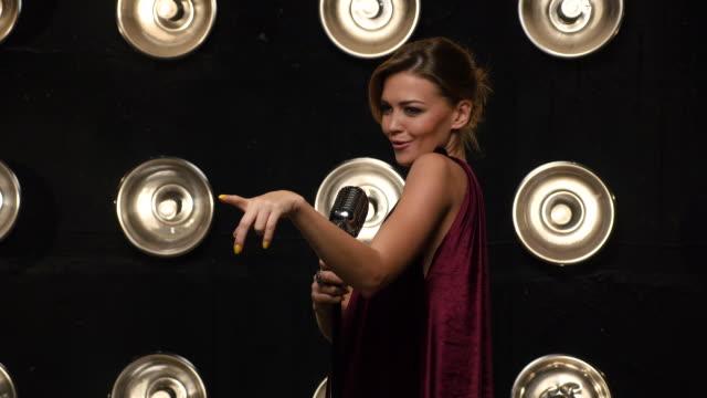 beautiful young female vocalist singing into retro microphone - adulazione video stock e b–roll