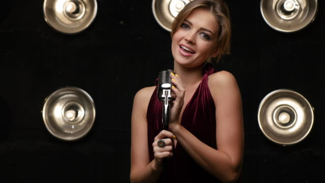 beautiful young female vocalist singing into retro microphone - stage performance space stock videos and b-roll footage