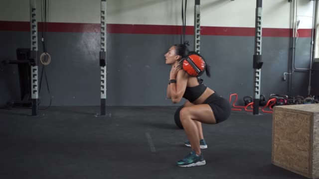 beautiful young fit woman at the gym doing crouches with a weight bag on her shoulders - crouching stock videos & royalty-free footage