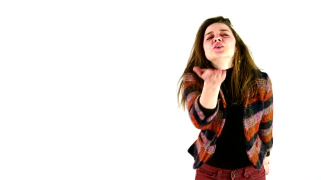 beautiful young girl blowing kisses to camera standing in front of a white studio background - lipstick kiss stock videos and b-roll footage
