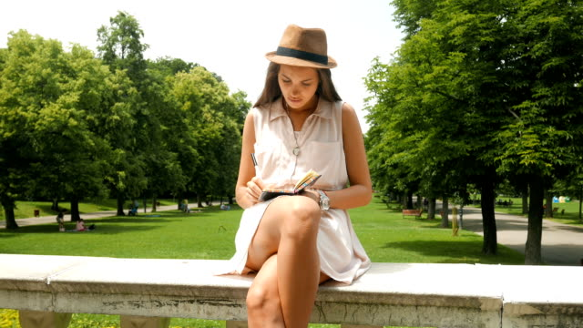 beautiful young girl hand writing in her diary outdoors - diary stock videos & royalty-free footage