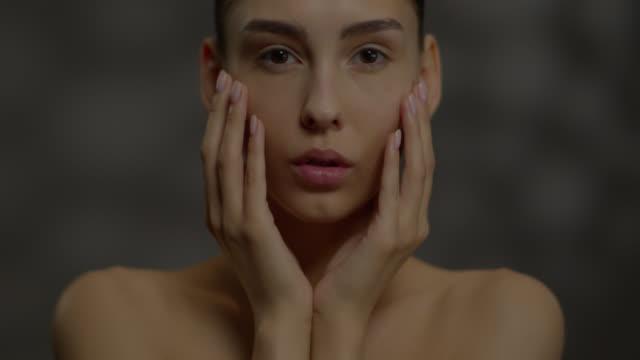 vidéos et rushes de belle jeune fille embrasse son visage avec ses mains et regarde la caméra. - cou humain