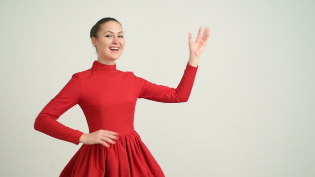 beautiful young girl in a red dress shows the copy space and shows okay on a gray background - hair bun stock videos & royalty-free footage