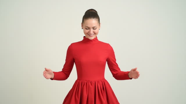 beautiful young girl in a red dress shows the copy space and shows his thumb on a gray background - hair bun stock videos & royalty-free footage