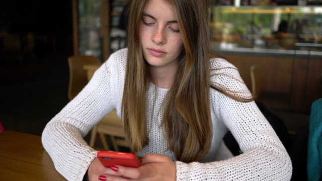vídeos de stock e filmes b-roll de beautiful young girl in cafe texting - meninas adolescentes