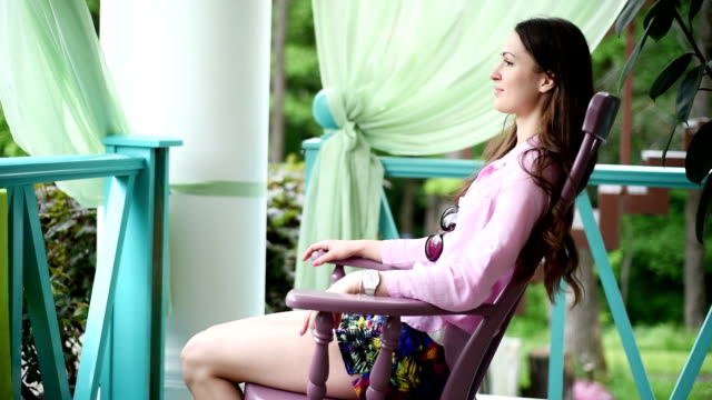 beautiful young girl sitting in a chair on the veranda