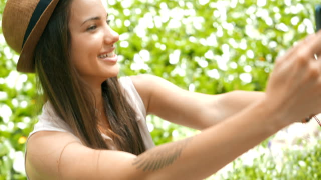 beautiful young girl taking selfies outdoors next to a water lily pond - day lily stock videos & royalty-free footage