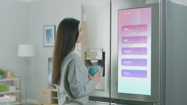 Beautiful Young Girl Walks Over to a Refrigerator While Drinking Her Morning Coffee. She is Checking the Weather Forecast and a To Do List on a Smart Fridge at Home. Kitchen is Bright and Cozy.