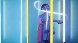 Beautiful Young Girl Wearing Virtual Reality Headset Draws Abstract Lines and Figures with Joysticks / Controllers. Creative Young Girl Does Concept Art with Augmented Reality. Neon Retro Lights Surround Her. Computer Graphics.