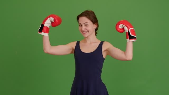 beautiful young girl with boxing gloves on a green screen. 4K