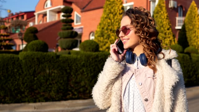 beautiful young girl with curly hair talking on her phone - curly stock videos & royalty-free footage