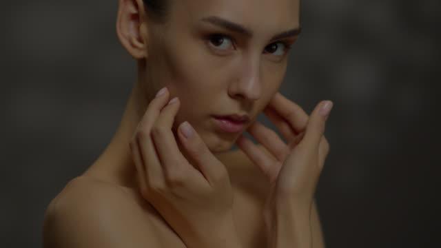 vidéos et rushes de belle jeune fille avec la bonne peau regarde l'appareil-photo. - cou humain